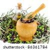 Olive oil, fresh olives  and  mortar  over white background. - stock photo