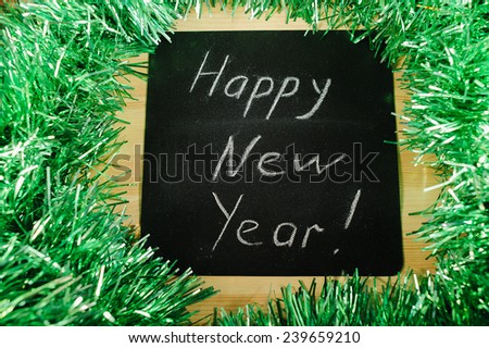 "on the black Board, white chalk written ""happy new year"" on the background of green tinsel. - stock photo"
