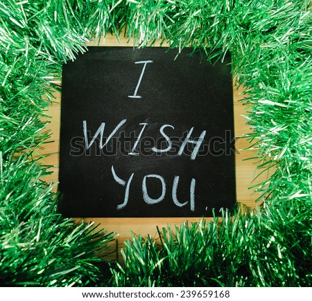 "on the black Board, white chalk written ""I wish you"" on the background of green tinsel. - stock photo"