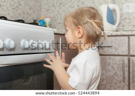 One child playing with   oven in   kitchen.