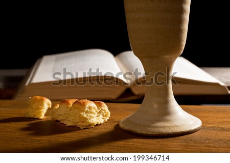 open bible and wine chalice - stock photo