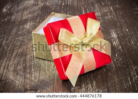 Open gift box with golden ribbon on the old wooden floor - stock photo
