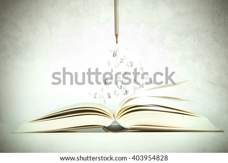 opened book with alphabet letter flying out of pages, vintage color tone - stock photo