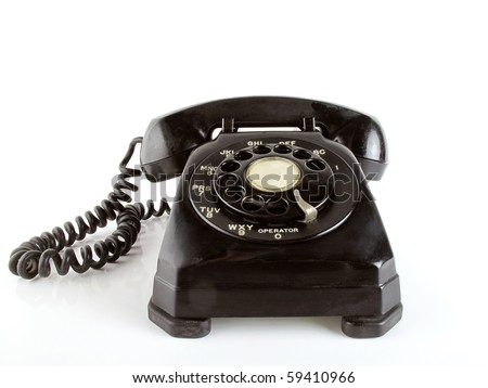 1950 or 1960 style black telephone sits on a white reflective surface