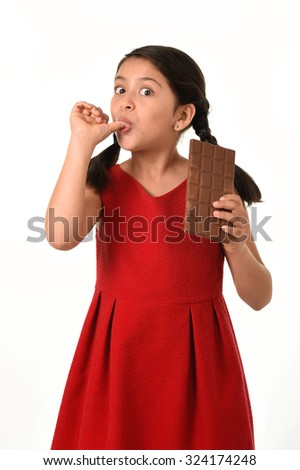 7 or 8 years old Hispanic girl wearing red dress holding big chocolate bar eating in happy and excited face expression licking her fingers in sugary nutrition and kids loving sweet concept - stock photo