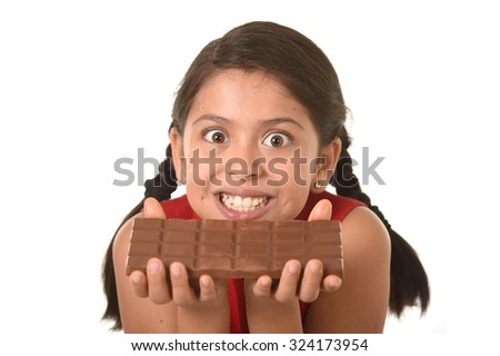 7 or 8 years old Hispanic girl wearing red dress holding with both hands big chocolate bar in front of her crazy excited face expression in sugary nutrition and kids loving sweet concept - stock photo