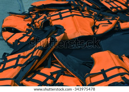 Orange color life jackets,  on the wall of the boating station  - stock photo