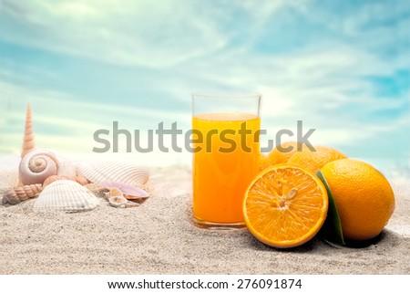 Orange slice and juice on the beach - stock photo