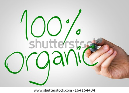 100% Organic hand writing with a green mark on a transparent board - stock photo