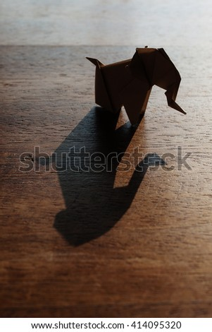 Origami elephant made of brown paper over wooden background. - stock photo