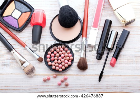 ?osmetics products on white. Cosmetics makeup artist objects: lipstick, eye shadows, powder, tools for make-up. Selective focus top view.