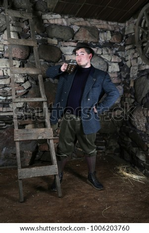 Ã?ountry style man drinks beer inside village barn interior on stone wall background