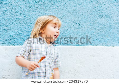 Outdoor portrait of a funny little toddler boy, holding candy, standing against blue wall