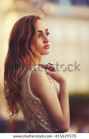 Outdoor portrait of a young beautiful fashionable lady posing on street. Model wearing stylish clothes. Girl looking aside. Female fashion. City lifestyle. Toned style instagram filters - stock photo