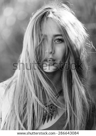 Outdoor sunny lifestyle portrait of happy pretty  women with windy  blonde hair  seriously   looking at camera ,  wearing  cool tropical accessories .Black and white.