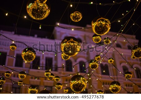 Outdoors city xmas decoration at the main square with lighting garlands and big golden bulbs