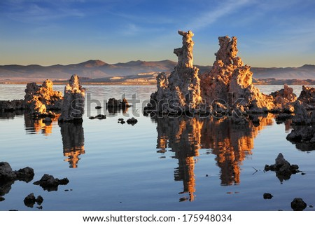 Outliers -  bizarre calcareous tufa formation  reflected in the mirrored surface of the water. The picturesque sunset at Mono Lake. Yosemite National Park, USA - stock photo