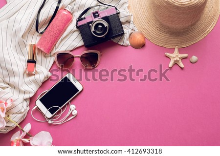 Overhead of essentials for modern student, teenager, woman. Top view of female fashion beach  accessories,straw hat, mobile phone with earphones, lipstick and body cream on bright pink background.  - stock photo