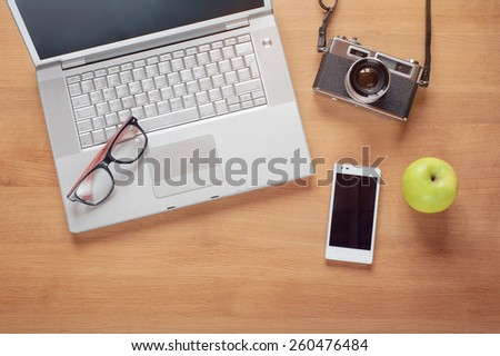 Overhead of modern comfort work place. Different objects on wooden background. Items include camera, glasses, laptop, smartphone and apple - stock photo