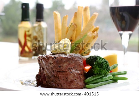 8 oz Tenderloin Steak topped with truffle butter. Served with broccoli, beans, horseradish and fries. Backdrop of a glass of red wine. Shallow DOF. - stock photo
