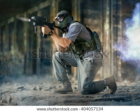 Paintball player in action with paintball gun  - stock photo