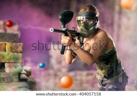 Paintball player shootout from marker gun - stock photo