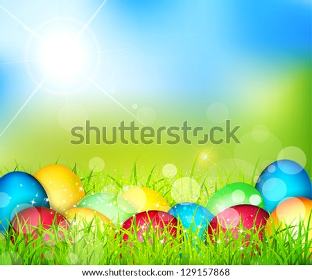 painted Easter eggs lying in the grass against the sky and the bright rays of the sun