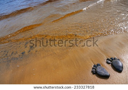 pair trace feet made of a pebble stone on the sea sandy coast, surface texture top view background                      - stock photo