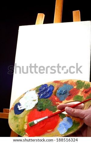 palette,  canvas and easel in black background  - stock photo