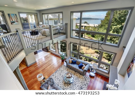 Panoramic View Of Elegant Grey Living Room From Upstairs High Vaulted Ceiling And Large Windows