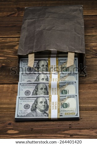 PAPER BAG WITH MONEY. Dollar banknotes coming out of a paper bag on old vintage wooden background - stock photo