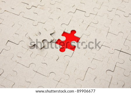paper puzzle background with one red piece missing - stock photo