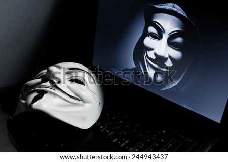 Paris - France - 18 January 2015 - Vendetta mask on computeur with an anonymous member on screen, . This mask is a well-known symbol for the online hacktivist group Anonymous