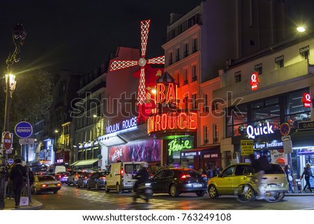 PARIS, FRANCE, on October 27, 2017. The well-known cabaret Moulin Rouge in evening lighting. Numerous cars go in the evening on the street lit with night illumination