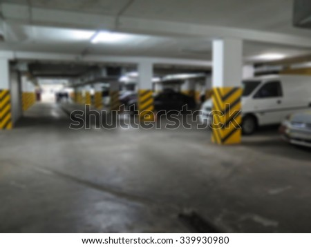 Parking garage, underground interior with a parked cars and people. Intentional motion blur                               - stock photo