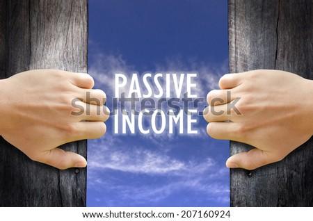 """PASSIVE INCOME"" text in the sky behind 2 hands opening the wooden door. - stock photo"