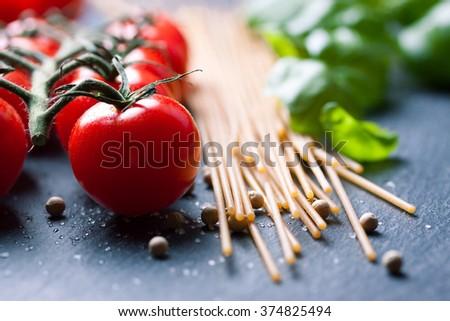 Pasta ingredients. Cherry-tomatoes, spaghetti pasta, fresh basil, spices on a dark stone background, closeup, selective focus  - stock photo