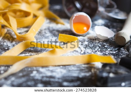 Pasta with flour and egg over black background, selective focus - stock photo