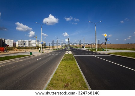 paved road that leads to the construction site where build a multi-storey houses - stock photo