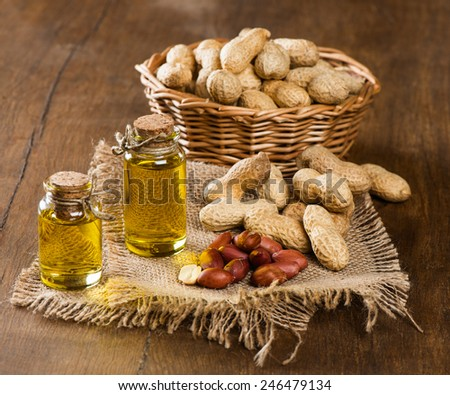Peanut oil in bottles and nuts on a wooden background - stock photo