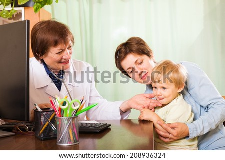 pediatrician doctor examing baby at clinic office   - stock photo
