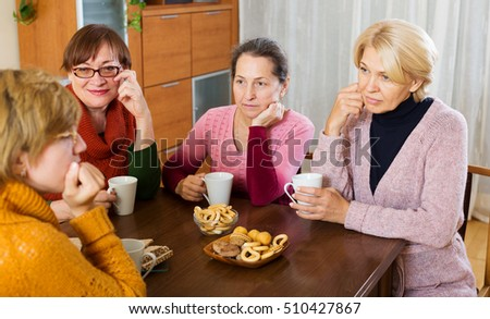 pensioners listening to sad story of their friend at table  indoor