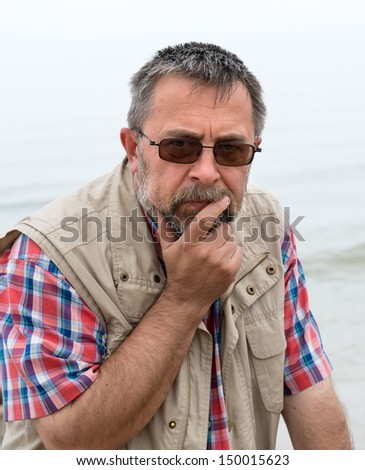 Pensive and sad looking elderly man on the beach