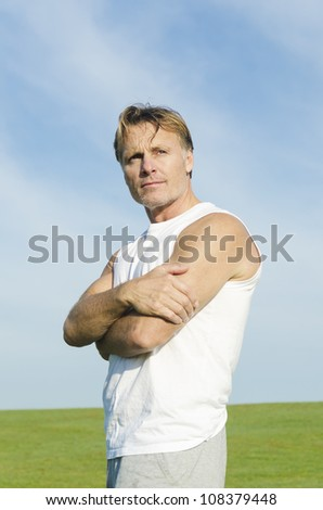 pensive looking man wearing a white tank top and grey shorts. - stock photo