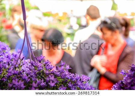 People buying flowers at Columbia Road Flower Market. London, UK. Selective focus. Blurred People. - stock photo