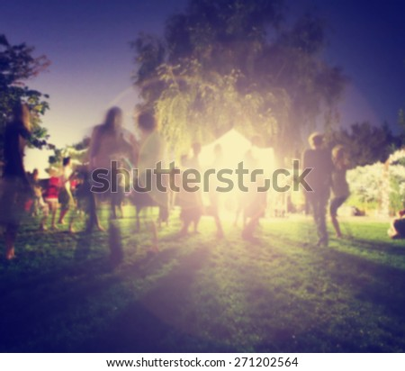 people mingling at a free concert by local musicians in a garden st night with a long exposure toned with a retro vintage instagram filter effect app or action - stock photo