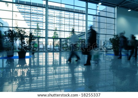 People moving in glass corridor - stock photo