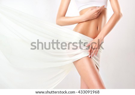 Perfect slim toned young body of the girl . An example of sports , fitness or plastic surgery and aesthetic cosmetology.   - stock photo