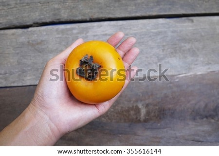 Persimmon on hand , selective  focus . - stock photo