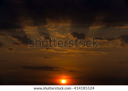 photographed a bright disk of the sun in the sky during sunset - stock photo